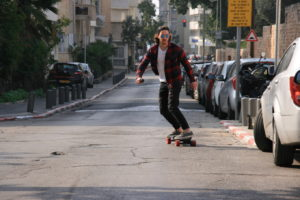 riding an electric longboard on the street to work