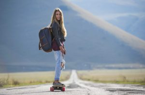 girl riding an electric longboard with a backpack