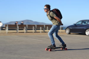 man riding electric longboard quickly with backpack