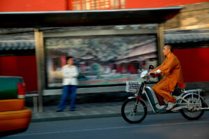 monk riding an electric bike in city