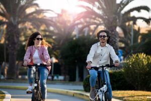 couple riding electric bikes together in park