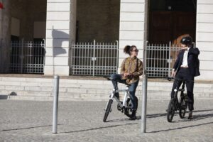 two people riding electric bikes talking