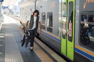man loading electric bike onto train public transport