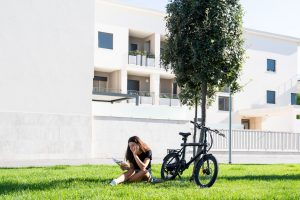 girl reading book under tree with electric bike good for the environment
