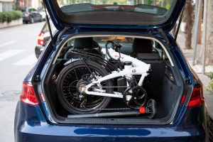 foldable bike placed into the back of a car in the city