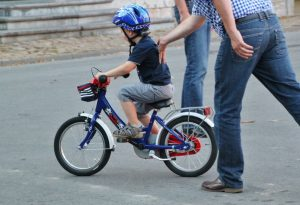young child learning how to ride bike with parents