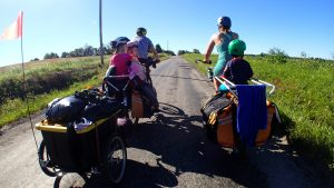 parents pulling kids in trailer with electric bikes