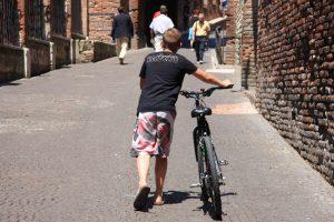 man walking bike up hill