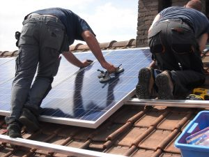 men installing solar panels on roof of home